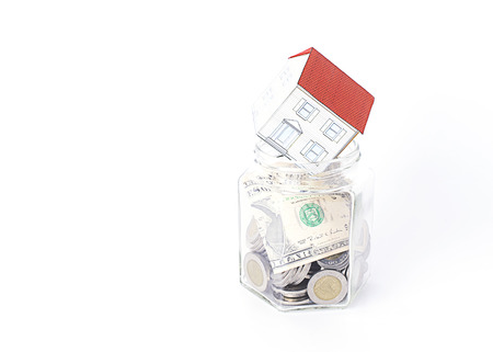loans: Paper house put on bottles glass for Mortgage loans concept Stock Photo