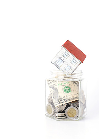 loans: Paper house put on bottles glass for Mortgage loans concept vertical Stock Photo