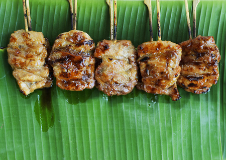 Grilled pork or mooping thai local street food on banana green leaf backgrounds above
