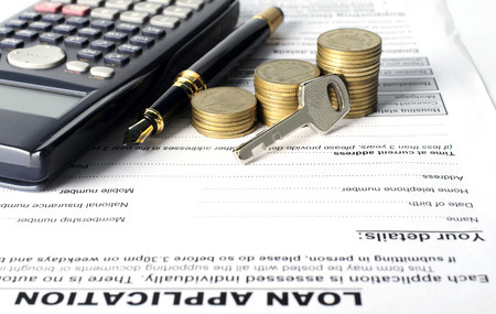 financial item: Home key with coins stack and business fountain pen and calculator on loan application document for finance ideas concept