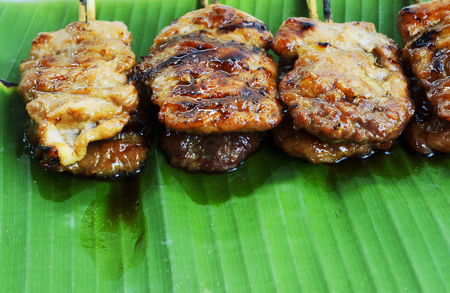 pierce: Close up of Delicious grilled pork mooping thai local street food on banana green leaf Stock Photo