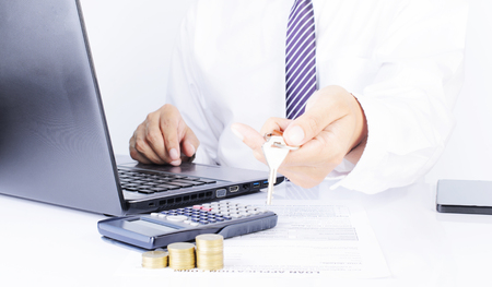 financial item: Business man hand holding key with laptop and calculator and coins on office desk for finance ideas concept