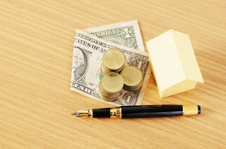 financial item: Fountain Pen and Dollar money and coins stack and Home paper for Loans concept