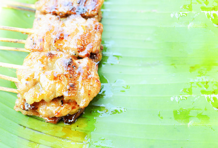 Delicious grilled pork on Mooping Thai local food on banana green leaf. Place for your text