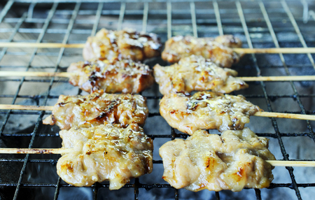 pierce: Grilled pork or Mooping Thai local food cooking on a coal Stock Photo