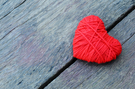 Red heart shape made from thread yarn on old wooden background for Valentines day concept Stock Photo - 93703561