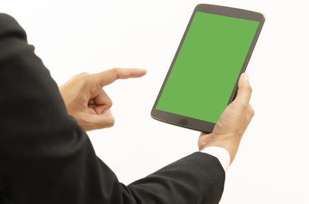 Business man using tablet with green screen on white backgrounds for copy space. Place for your text