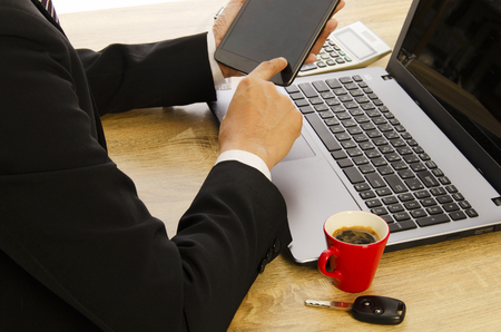 Business man hand holding tablet, labtop on wood table desk with car key and red coffee cups