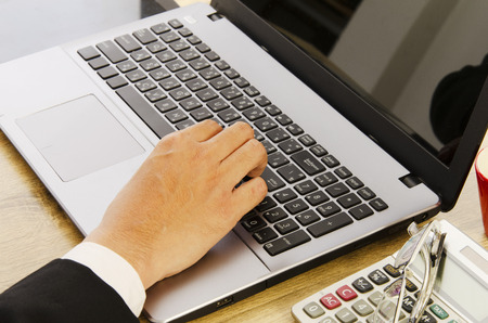 Close up of Business man hand typing keyboard laptop computer on office desk table Banco de Imagens