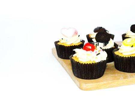 Close up van smakelijke cup cake op een houten bord op een witte achtergrond