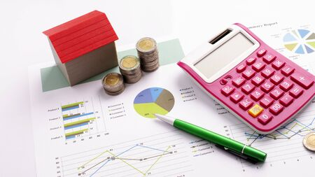 Mortgage loans concept with red house and coin stack, calculator and pen on business report backgrounds