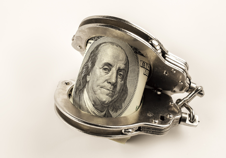 handcuffs: dollars and police handcuffs on a white background Stock Photo