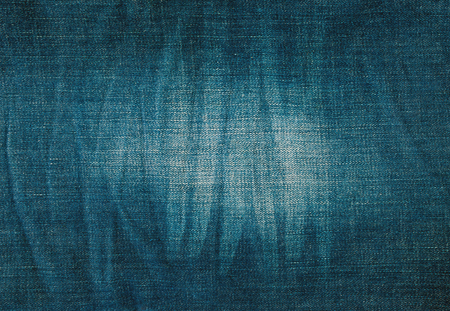 scuffed: background texture of blue jeans with pleats and scuffed