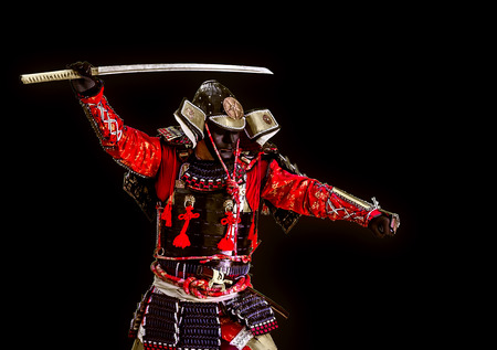warriors: Samurai in ancient armor close-up with a sword attack