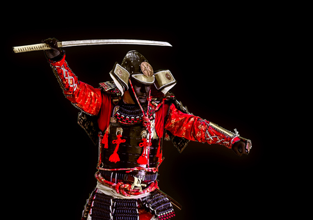 Samurai in ancient armor close-up with a sword attack