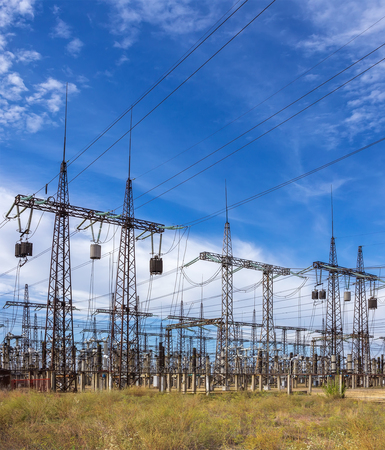 electricidad industrial: distribuci�n subestaci�n el�ctrica con l�neas de alta tensi�n sobre un fondo del cielo de verano Foto de archivo