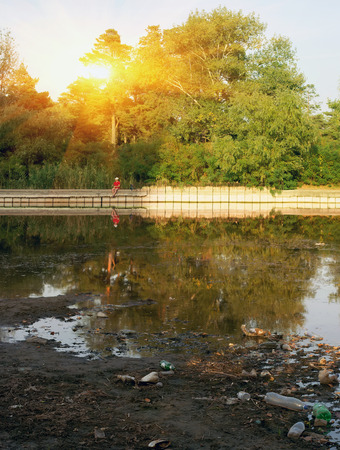 decompose: garbage on the waterfront at sunset in the pine forest. pollution ecology Stock Photo