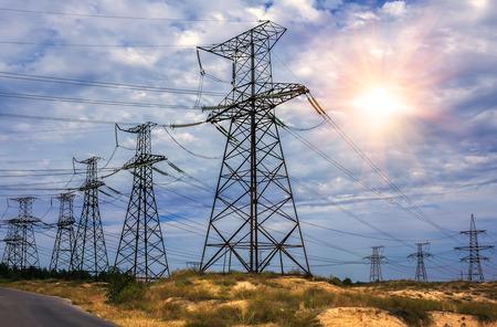 High-voltage power lines tegen de achtergrond van een stormachtige hemel met de zon