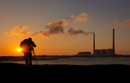 power giant: photographer at sunrise on the coast, on a background of giant pipes power