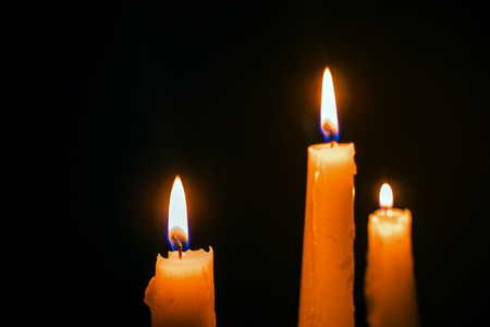 Three burning wax candles on a black background. Christmas, religion