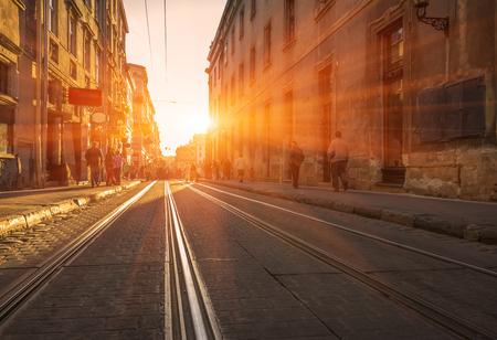 oude straat met straatstenen en tramrails bij zonsondergang. Oude stad Stockfoto
