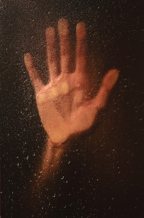 lean on hands: hand on a wet window with raindrops. loneliness