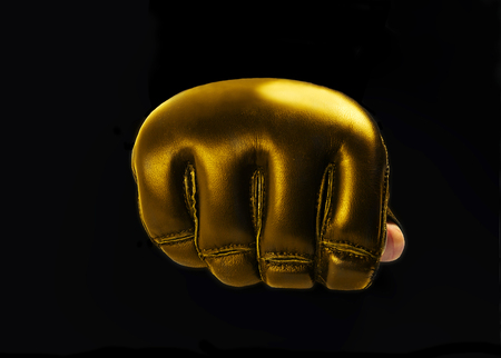 mma: fist gold gloves for martial arts, mma on a black background