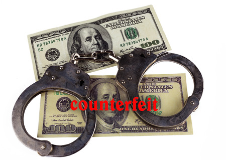 police handcuffs false and real hundred-dollar bill. the concept of counterfeiting of money and punishment. Фото со стока