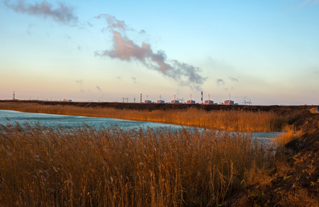 nuclear power plant: huge nuclear power plant on the background of the pond with reeds at sunset. pollution. Stock Photo