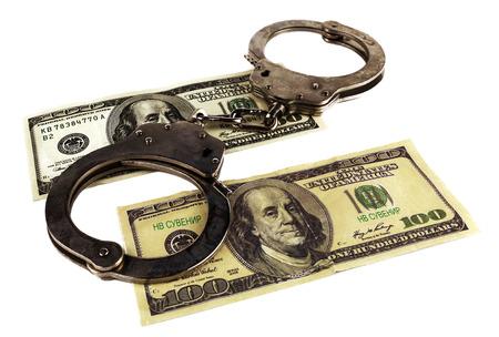 counterfeiting: Handcuffs on dollar bills. fake dollars, bribery, fraud.