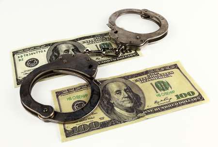 counterfeiting: fake dollars with handcuffs isolated on white background.