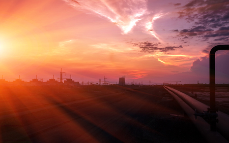 npp: industrial background with pipes against a red sunset.