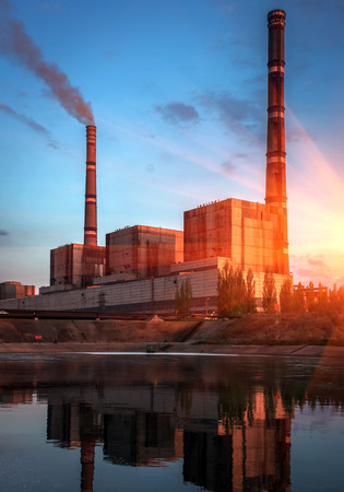 tall chimney: factory with huge pipes in the reservoir reflection at sunset. vertical. Stock Photo
