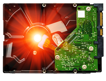 microcircuit: computer hard drive with printed motherboard and microcircuit  in the rays Stock Photo