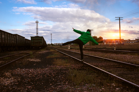 complicated journey: man travels on rails danger, against the background of beautiful sky.