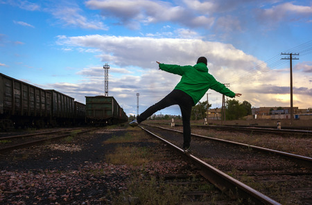 complicated journey: man travels on rails, against the background of beautiful clouds.