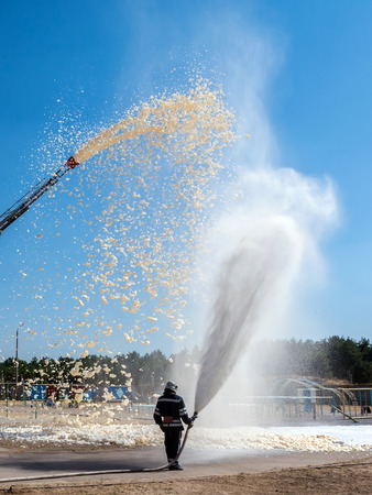 firefighter holding a fire hose with water pressure, a demonstration of fire fighting equipment. Stock Photo