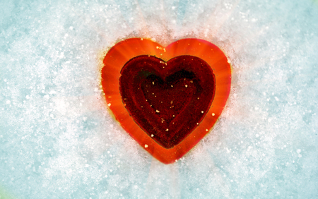 Red heart on a background of snow. Happy Valentines day. Stock Photo