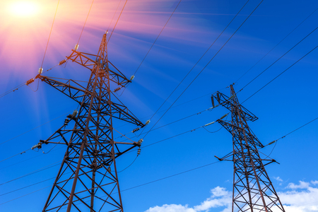 metal grid: High-voltage lines against the blue sky at sunset. electricity