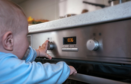 dangerous situation, the child is playing with an electric stove. The child plays near a hot stove. Stok Fotoğraf
