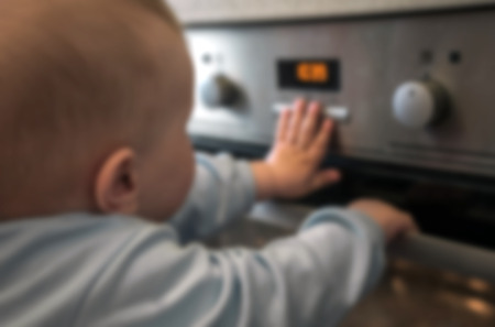 dangerous situation, the child is playing with an electric stove. The child plays near a hot stove. Reklamní fotografie