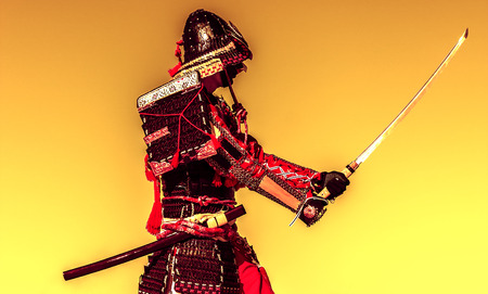 Samurai in ancient armor, with a sword ready to attack close-up Stock Photo
