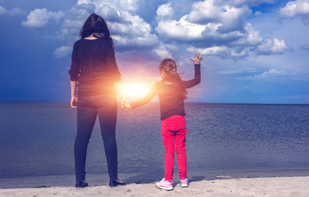 young mother with her daughter on the beach at sunset