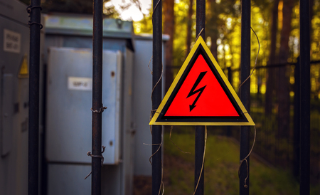 High voltage sign on a fence, on a background of transformers at sunset. top view.