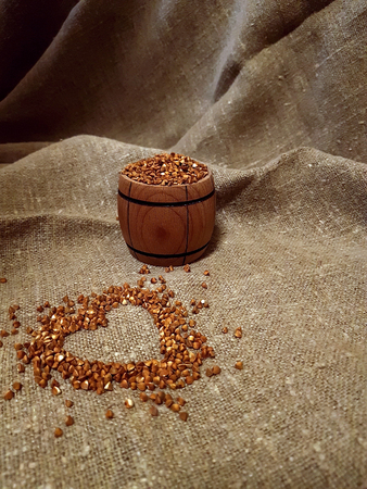 grains of buckwheat, drawing of a heart on burlap, rural background. Organic, diet food.