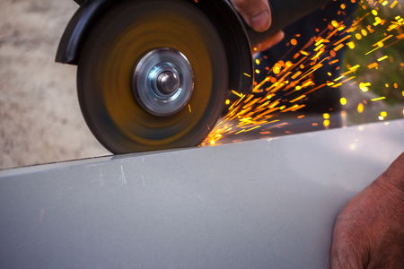 A builder cuts a metal structure with a grinding machine.