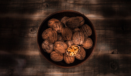 nuts, healthy nutritional food. walnut close-up in a clay bowl on a wooden background.