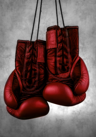 red boxing gloves hanging on the wall, close-up. motivation in sport.