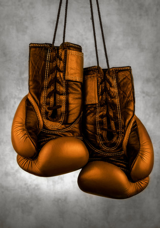 gold boxing gloves hanging on the wall, close-up. motivation in sport.