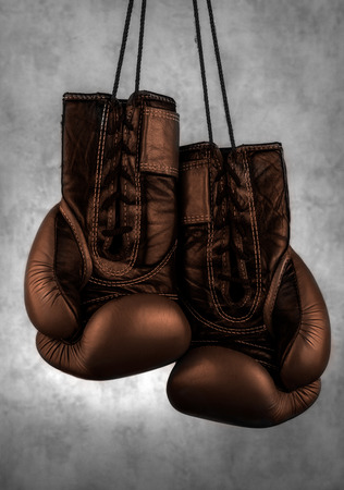 brown boxing gloves hanging on the wall, close-up. motivation in sport.
